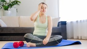 Tired sweaty woman resting on fitness mat at home. Tired sweaty woman resting on fitness mat stock photography