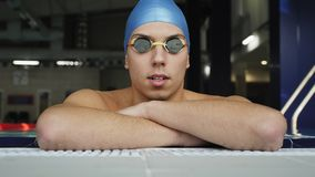 The tired swimmer rests in the pool. The guy is resting leaning on the side of the pool. Young male swimmer in the pool. The tired swimmer rests in the pool stock video