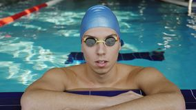 The tired swimmer rests in the pool. Young male swimmer in the pool. Swimmer is resting leaning on the side of the pool stock video footage