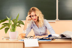 Tired teacher checking the tests. Royalty Free Stock Photo