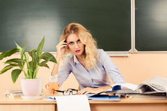 Tired teacher checking the tests. Stock Photos