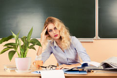 Tired teacher checking the tests. Royalty Free Stock Image