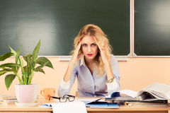 Tired teacher checking the tests. Stock Photography