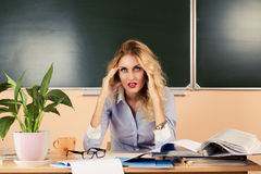 Tired teacher checking the tests. Royalty Free Stock Photos