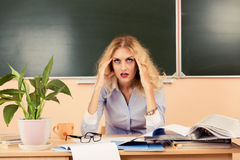 Tired teacher checking the tests. Back to school concept stock photos