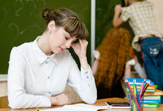 Tired teacher in classroom Royalty Free Stock Image