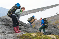 Tired team of backpackers in mountains Royalty Free Stock Photo