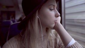Tired teen girl portrait looking outside through train window. Tired teen girl portrait looking outside through electric train window stock video