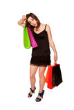 Tired teen girl with shopping bags leaving the store. Royalty Free Stock Image