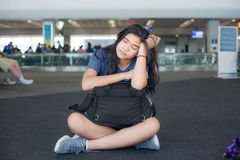 Tired teen girl sitting on floor at airport with luggage Royalty Free Stock Photo