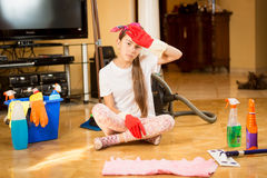Tired teen girl sitting on floor after cleaning living room stock images
