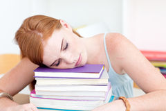 Tired teen sleeping on books after studying Stock Photo