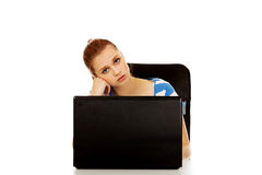 Tired teen woman with laptop sitting behind the desk Royalty Free Stock Photos