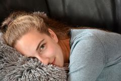 Tired teenage girl relaxing on the sofa stock images