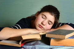Tired teenage girl sleep among books Royalty Free Stock Photos