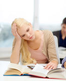 Tired teenage student with tablet pc and books Royalty Free Stock Photos
