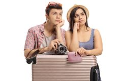 Tired teenage tourists leaning on a suitcase. Isolated on white background Royalty Free Stock Photo