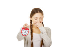 Tired teenage woman with alarmclock. Stock Photography