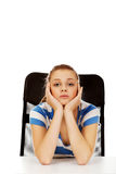 Tired teenage woman sitting behind the desk Stock Photography