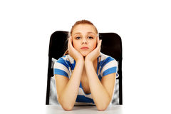 Tired teenage woman sitting behind the desk Royalty Free Stock Photography
