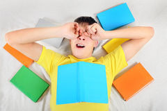 Tired Teenager with a Books. Tired Teenager Yawn with a Books on the Bed Royalty Free Stock Images