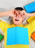 Tired Teenager with the Books. Tired Teenager yawning with a Books on the Bed Royalty Free Stock Photos
