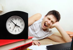 Tired Teenager doing Homework. And Yawning at the Home. Focus on the Clock Royalty Free Stock Photography