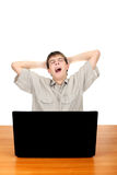 Tired Teenager with Laptop. Tired Student Yawning at the Desk with Laptop Isolated on the White Stock Photo