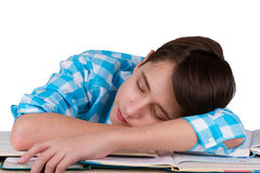 Tired teenager sleeps over the books after doing a homework. Stock Images