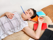 Tired Teenager on Sofa. Tired Teenager on the Sofa with the Books at the Home Royalty Free Stock Photos