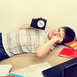 Tired Teenager on Sofa. Toned Photo of Tired Teenager on the Sofa hold the Clock Royalty Free Stock Photography
