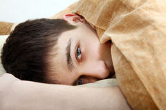 Tired Teenager Under Blanket Stock Image