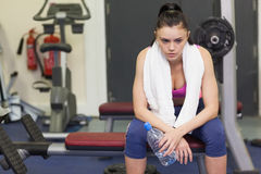 Tired and thoughtful woman in gym Royalty Free Stock Photos
