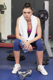Tired and thoughtful young woman sitting in gym Stock Image