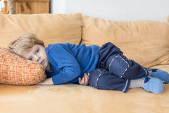 Tired toddler boy laying on couch Royalty Free Stock Photography