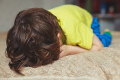 Tired toddler boy lying on the bed with his face down. Crying little kid. Tired toddler boy lying on the bed with his face down Royalty Free Stock Photos