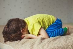 Tired toddler boy lying on the bed with his face down. Crying little kid. Tired toddler boy lying on the bed with his face down Stock Photos