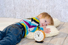Tired toddler lying down with alarm clock in front Royalty Free Stock Images