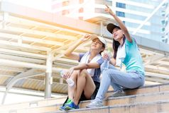 Tired after tough work out. young women sitting on the s. Tired after tough work out. Smiling young women sitting on the stairs and looking something royalty free stock image