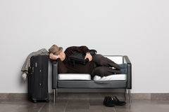 Tired tourist in anticipation of landing on aircra. Ft (ferry, train or bus). Flight delay due to weather conditions. Waiting hall Royalty Free Stock Photo