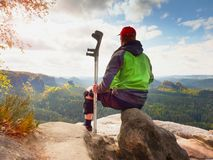 Tired tourist with medicine crutch  and broken leg fixed in immobilizer resting on summit. Royalty Free Stock Photography