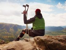 Tired tourist with medicine crutch  and broken leg fixed in immobilizer resting on summit. Stock Photos