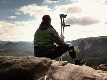 Tired tourist with medicine crutch  and broken leg fixed in immobilizer resting on summit. Stock Photography