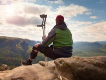Tired tourist with medicine crutch  and broken leg fixed in immobilizer resting on summit. Royalty Free Stock Photo