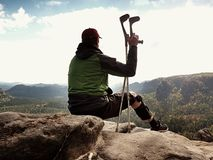 Tired tourist with medicine crutch  and broken leg fixed in immobilizer resting on summit. Stock Images
