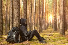 Tired tourist is resting in the forest. Traveler man at halt. Copy space royalty free stock photography