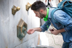 Tired tourists drinking water fountain Royalty Free Stock Photography