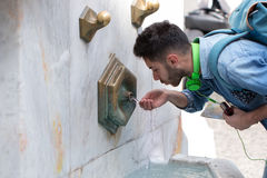 Tired tourists drinking water fountain Royalty Free Stock Photos