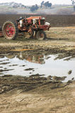 Tired Tractor. A worn out old tractor sitting next to a mud puddle stock photography