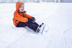 Tired at training exercise boy teen on snow near skating ice rink in hockey skate royalty free stock photos